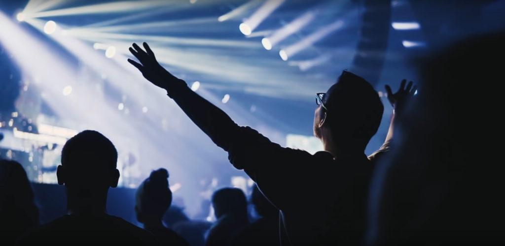 Best Aftermovie Fan der die Hände nach oben ausgestreckt hat mit Bühne im Hintergrund